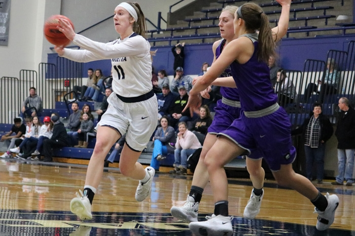 Women's basketball player receives a pass in the post with two defenders