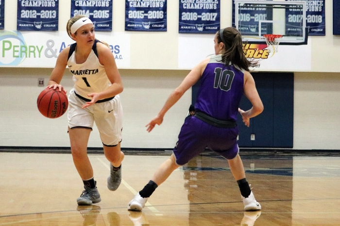Female basketball player dribbling the ball as an opponent applies defensive pressure