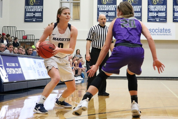 Women's basketball looking to pass as a defender applies pressure