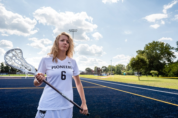 Women's lacrosse player holding a stick on the field