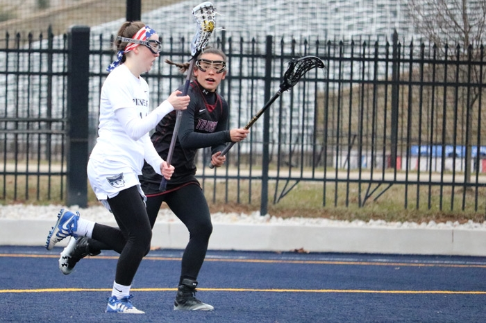 Women's lacrosse player running with the ball while trying to escape a defender