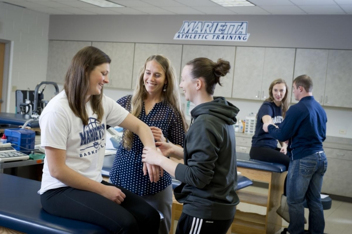 An Athletic Training professor works with students in the hands-on classroom