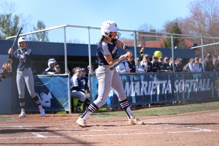 Softball player swinging at a pitch
