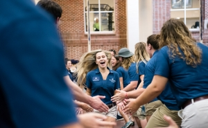 Marietta College Orientation Leader runs through the crowd at PioSOAR 2017