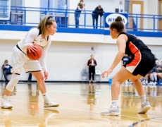 Female basketball dribbling while being defended