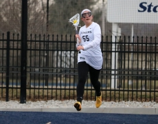 Women's lacrosse player running with stick and ball
