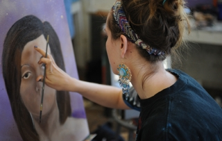 A Marietta College student puts the finishing touches on a portrait