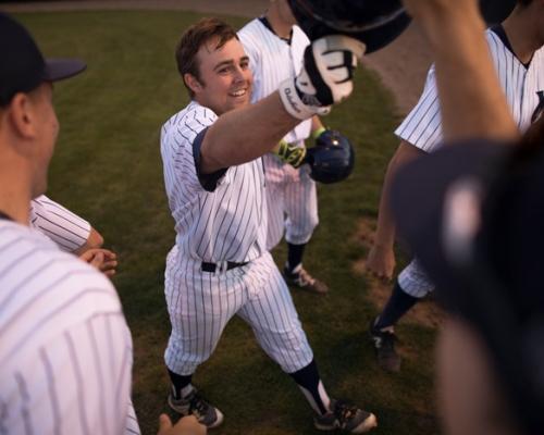 Marietta baseball player being congratulated after hitting a home run.