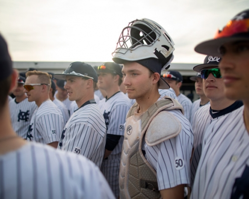 Marietta catcher surrounded by teammates before taking the field