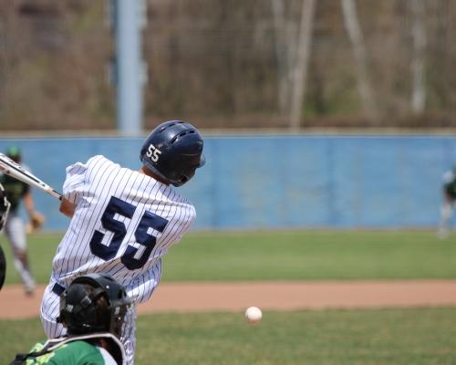 Baseball player following through on a swing as the ball heads toward third base