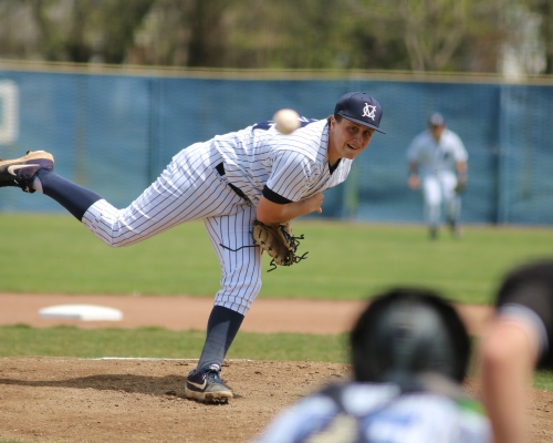 Baseball player delivering a pitch to the plate