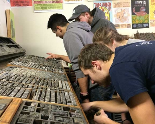 Students look for metal stamps at justAjar in downtown Marietta