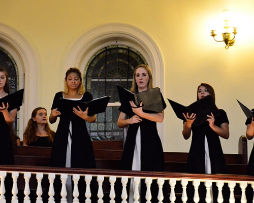 Female students singing in balcony at church