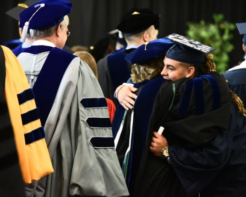 Senior Roger Walker hugging a faculty member