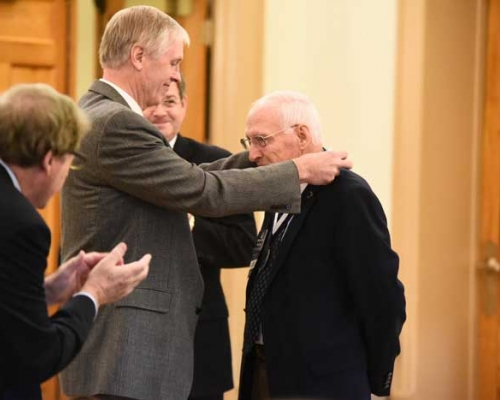 BOT chair George Fenton places the Presidential Medal on Tim Cooper
