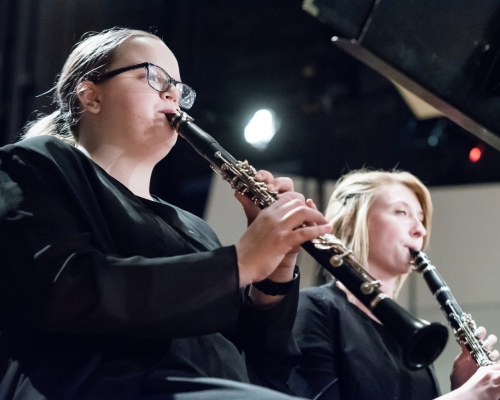 Two females playing clarinets
