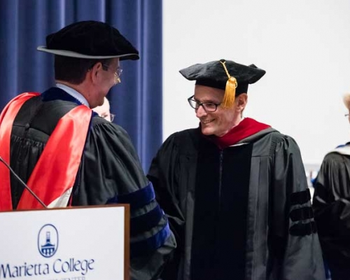 Dr. David Torbett shakes hands with President Ruud at Founders Day