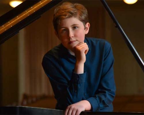 Gavin George posing at piano