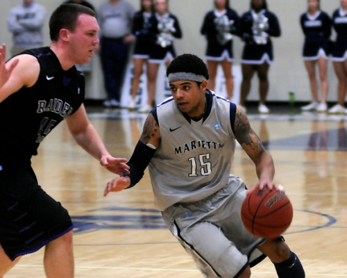 Tyler Hammond dribbles the basketball around a Mount Union defender during his Marietta College playing career