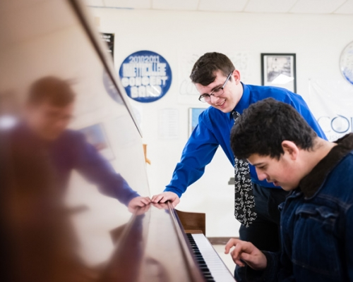 Students playing a piano