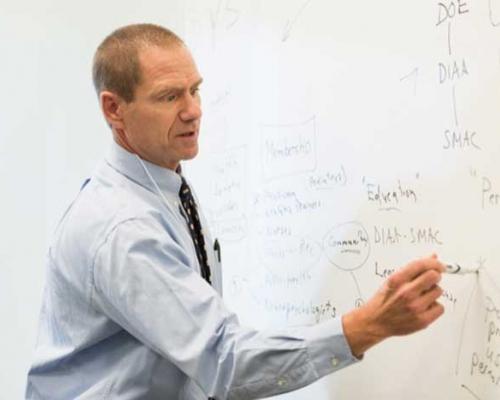 Tom Kaminski writing on erase board