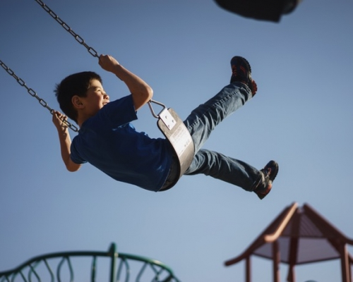 Young boy swinging on a playground swing