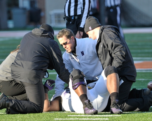 Northwestern's Tory Lindley assisting an injured football player