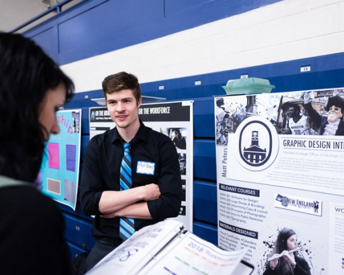 Male student standing next to poster at presentation