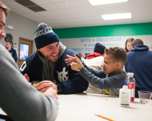 A Marietta College baseball player laughs with a child at the Boys & Girls Club