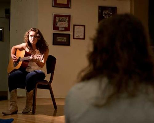 Sadie Johnson playing guitar in Izzy's