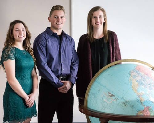 3 Marietta students standing behind a large globe