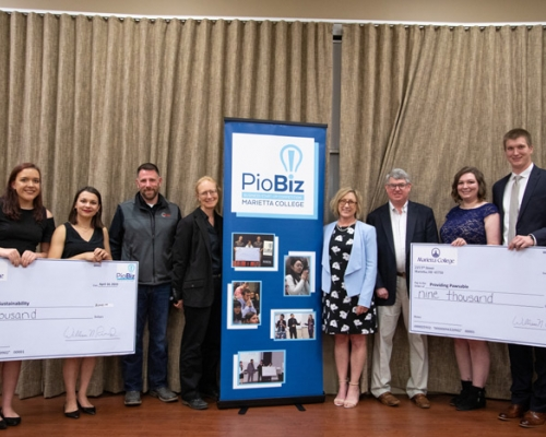 PioBiz winners posing with checks and the judges
