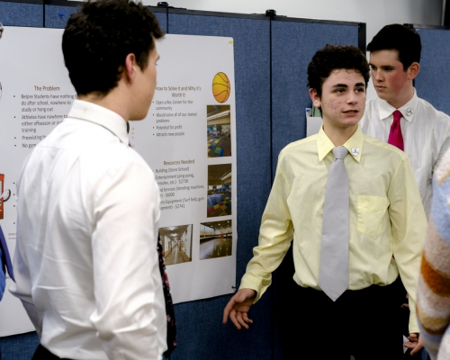 Male high school student wearing ties and dress shirts making a presentation