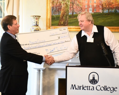 President Ruud shakes the hand of David Goldenberg during a check presentation