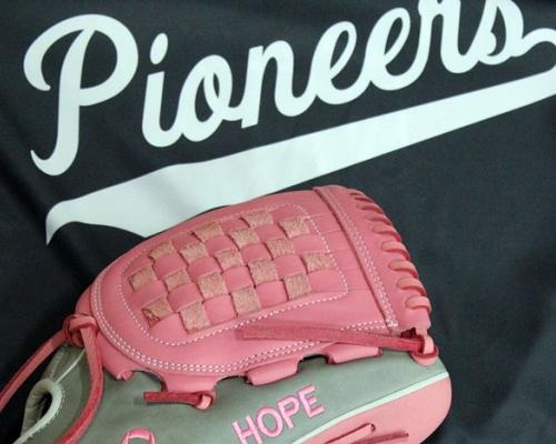 Pink softball glove on top of a softball jersey