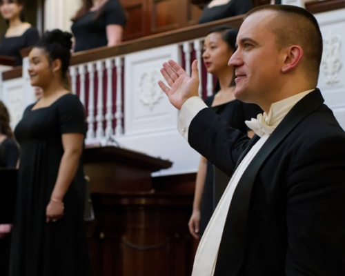 Choral director acknowledging the women's choir after singing