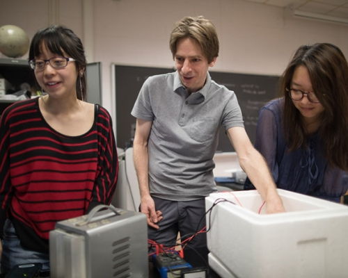 Two female students conducting an experiment with a faculty member
