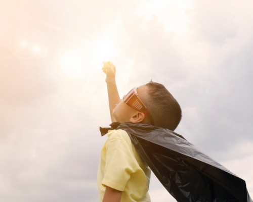 Young boy wearing a cape and looking toward the sky