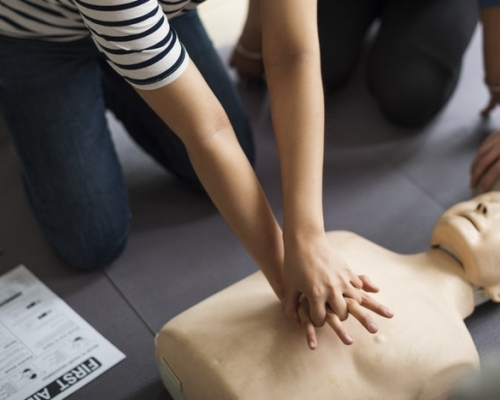 Person performing CPR on a manikin