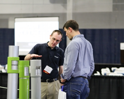 White male speaking with a male student at the oil and gas expo