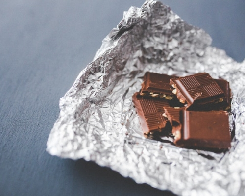 Dark brown milk candy bar on a foil wrapper