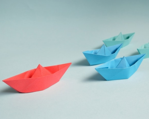 Paper boats with a single red one in front