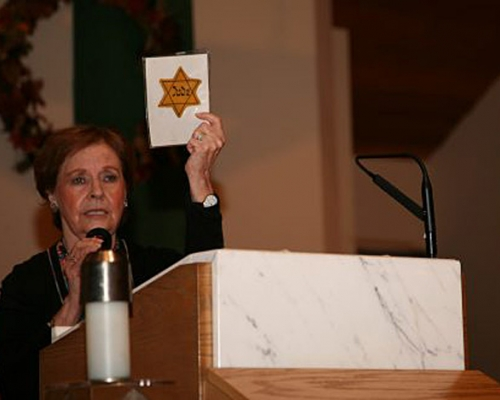 Marion Blumenthal Lazan speaking behind a podium and holding up a Jewish star