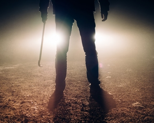 scary man holding tire iron with lights in the background