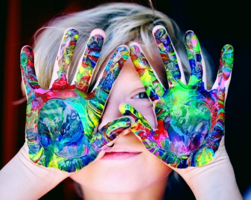 Child with painted hands in front of face