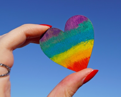 female hand holding a multi-color heart