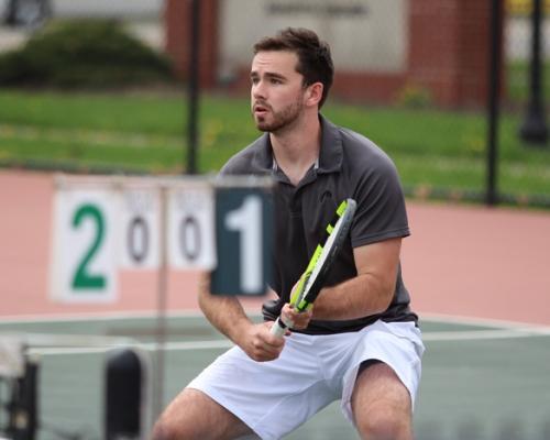 Men's tennis player charging the net