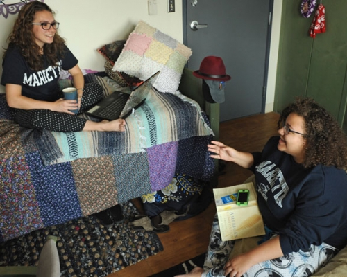 Two female students in a dorm room