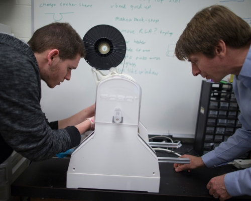 Dr. Craig Howald working with a student on a 3D printer