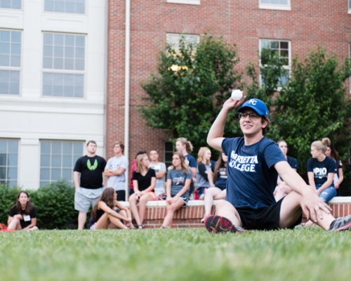 Male sitting and throwing a ball in front of Harrison Hall
